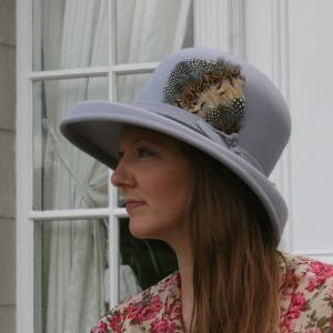 Large silver peach bloom hat with multicoloured feather