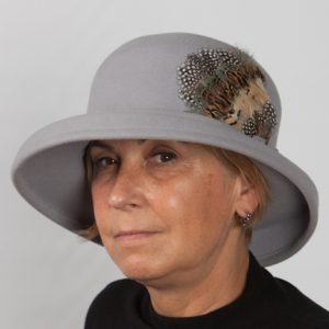 Smokey grey felt hat with brim and a felt band around crown with multicoloured feather to the side
