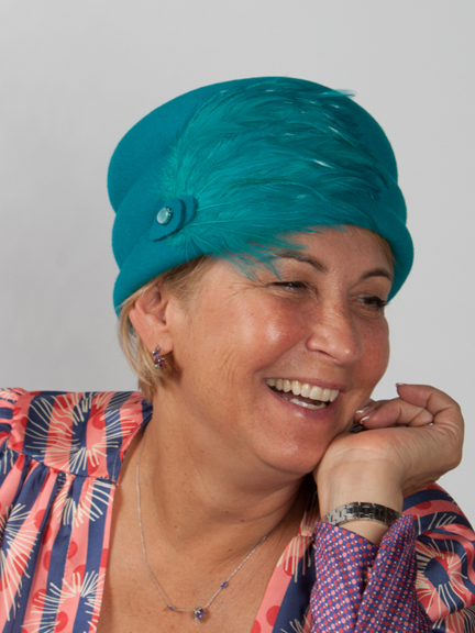 Front view of a turquoise pill box hat with large feather pad to the sider