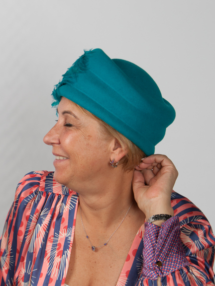 Side view of turquoise wol felt hat with large feather detail to the side