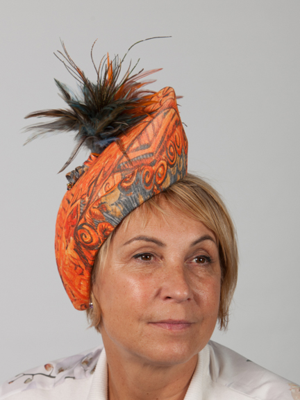 Front view of an orange hat with featherdetail worn to the side