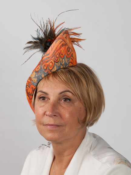 Side view of an occasion hat in orange and touch of blue with feather detail.