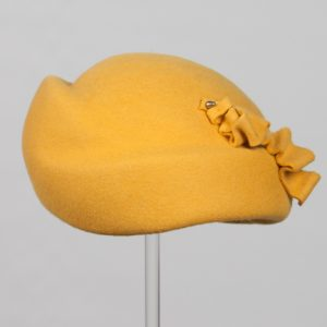 Front view of mustard wool felt hat with felt design detail to the side.
