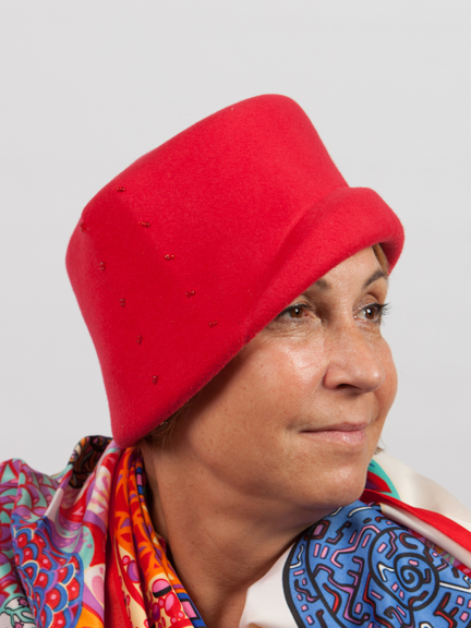 Side view of a red felt hat with bead design to the side