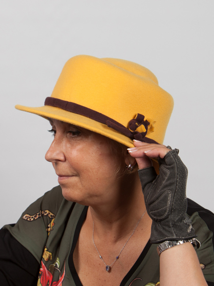 Side view of yellow wool yellow felt hat with wine band around crown and win and yellow detail to the side.