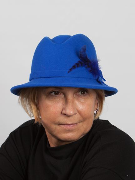 Front view headshot royal blue wool felt hat will small brim and indent on the top with navy feather the side.