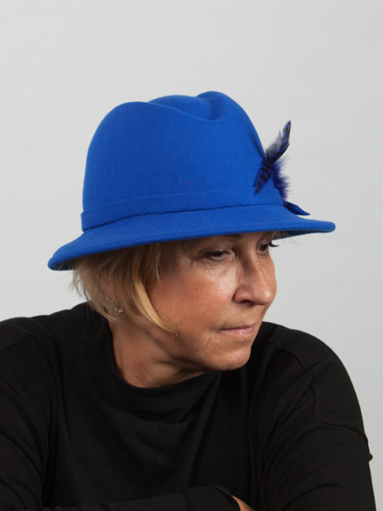 Side view headshot royal blue wool felt trilby with small maching felt band around crown and navy blue feather to the side.