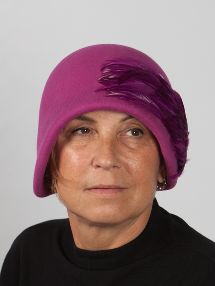 Front view headshot of woman in a fushia cloche wool felt hat with fushia feather pad to the side