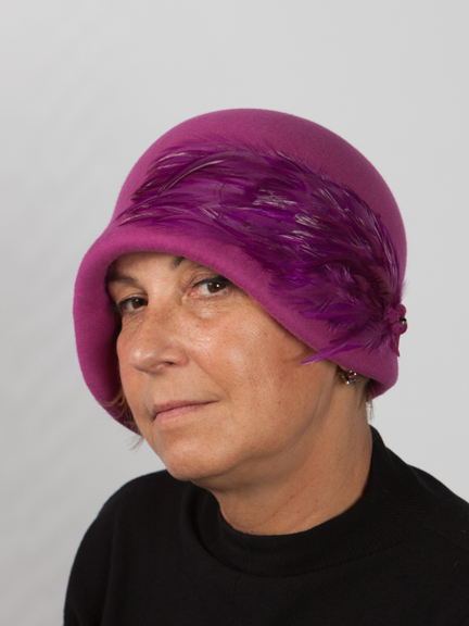 Side view headshot of a felt fushia cloche hat wit fushia feather pad to the side