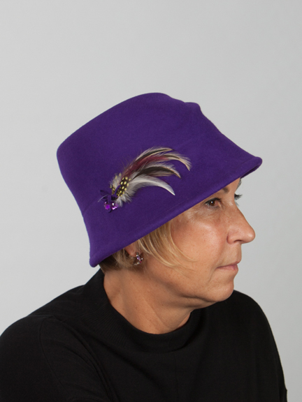 Side view headshot of purple woo felt hat with crease on the top and feather detail on the side