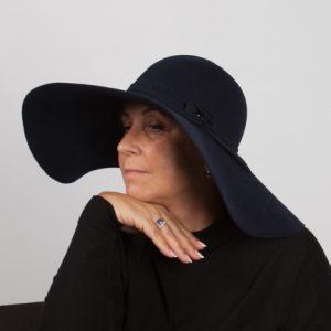 Side view headshot of large navy floppy fur felt hatt
